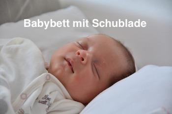 Baby schläft in Babybett mit Schublade