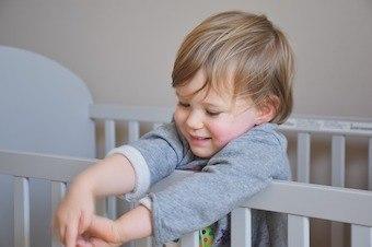 Kind im Kinderbett zum Umbauen
