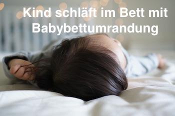 Kind schläft im Bett mit Babybettumrandung
