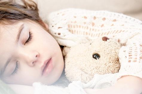 Kind schläft mit Teddy im Kinderbett