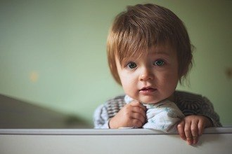 Kind steht im Kinderbett mit Rausfallschutz