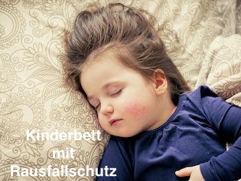Kind schläft im Kinderbett mit Rausfallschutz