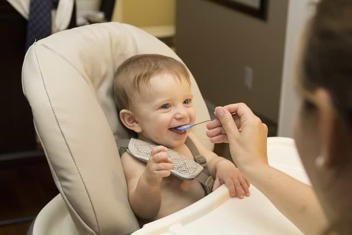 Baby in Babywippe mit Hochstuhl